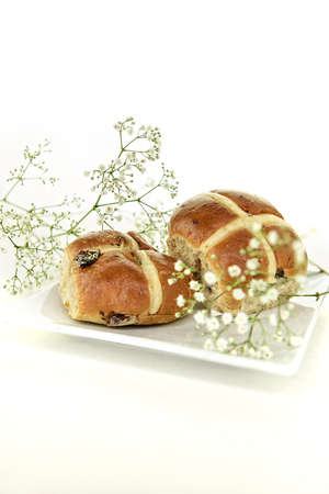 Two fresh hot cross buns a traditional Easter holiday treat shot with selective focus with Gypsophilia flowers with generous accommodation for copy space. Suitable image for your breakfast menu cover art. Stock Photo