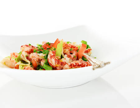 Close up of crayfish tail salad with lettuce, chives and tomatoes shot against a white background with generous accommodation for copy space.
