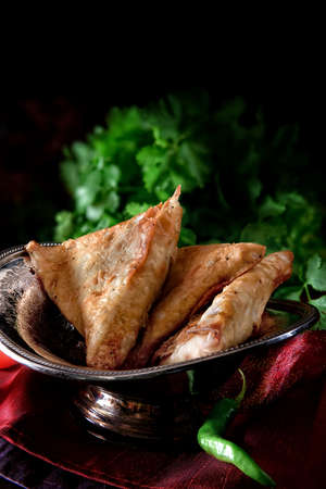 Authentic restaurant styled vegetarian genuine Indian samosa appetizer, shot against a dark background with cilantro (coriander) background with green chillies. Copy space. Stock Photo