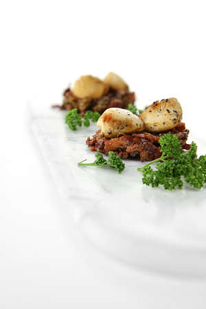 Seared scallops on warm caramalized smoked pork bacon with parsley herbs. Shot against a white background with generous accommodation for copy space. Stock Photo