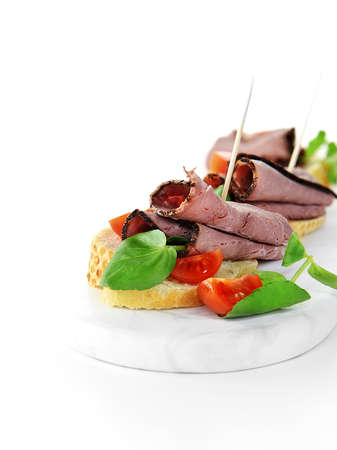 Prime roast beef slices with watercress salad and cherry tomatoes on sliced baquette secured with cocktail sticks. Concept image for wedding receptions, buffet and party food. Copy space.