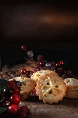 Seasonal festive traditional mince pies with marinated brandy filling shot against a dark rustic background with generous accommodation for copy space.