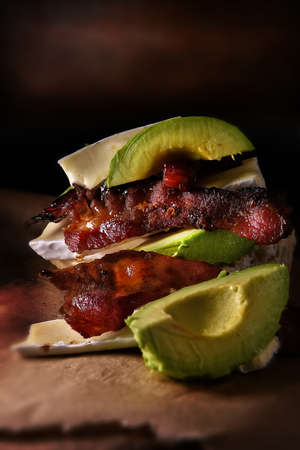Delicious smoked pork bacon rashers drenched in Canadian Maple Syrup stacked with organic produced French Brie cheese and ripe, organic grown sliced avocado - the perfect image for your bistro menu cover art.
