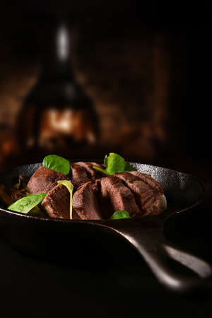 Wild venison fillets roasted with garlic mushrooms, scallions and watercress salad in a wrought iron black skillet shot against a rustic wood burner background with copy space.