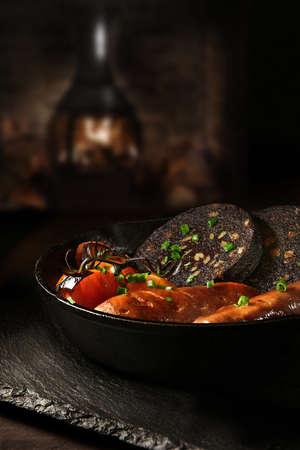 Traditional British savoury dish of Black Pudding with sauasages and grilled vine tomatoes in a wrought iron skillet shot against a rustic background with a roaring wood burner. Copy space. 免版税图像