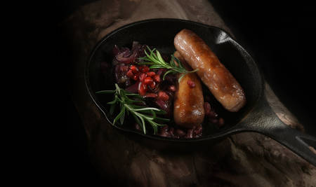 Overhead view od grilled pork sausages with caramalized red onions and pomegranites in a wrought-iron black skillet shot against a dark background with accommodation for copy space.