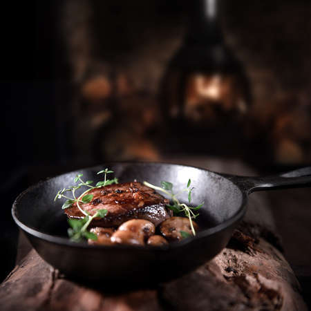 Fillet of venison, sliced and roasted with thyme herb garnish and garlic mushrooms, ready for serving in a wrought iron skillet shot against a rustic background with copy space.