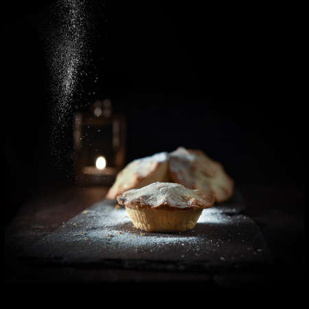 Selective focus on festive traditional mince pie shot against a dark festive background with accommodation for copy space. Soft sifted frosting adds to the seasonal effect for home baking.