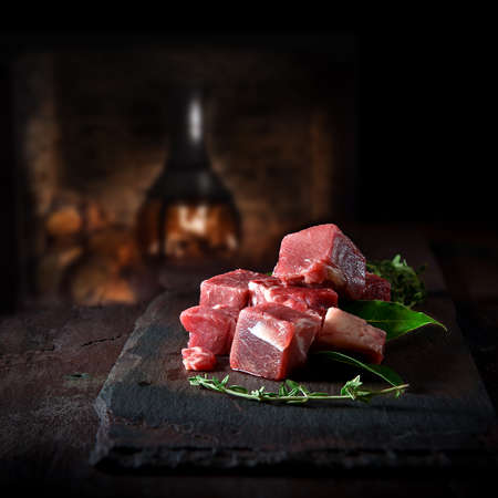 Creatively lit fresh raw cube diced red beef meat prepared for cooking on black slate, with thyme and bay leaves, shot against a dark, rustic background with accommodation for copy space.