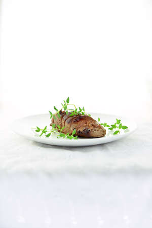 Wild fillet of venison, grilled, carved and served for eating with fresh green thyme garnish, shot against a white background with accommodation for copy space. Stock Photo