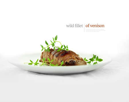 Wild fillet of venison, grilled, carved and served for eating with fresh green thyme garnish, shot against a white background with accommodation for copy space. Displayed text can easily be removed.