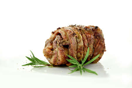 British rolled lamb rosted and served with rosemary herb garnish. Shot against a white background with generous accommodation for copy space. Stock Photo