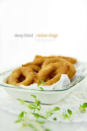 Deep fired onion rings in batter, shot against a white background with copy space. The display text can be easily removed and replaced with your own.
