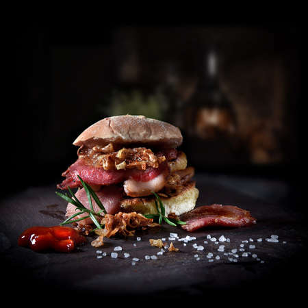 Delicious rustic smoked bacon burger with caramelized onions served with tomato ketchup and rosemary herb garnish. Shot against a dark farmhouse background with copy space.