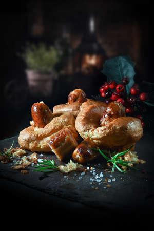 Fayre británica tradicional, comida reconfortante pasada de moda y muy popular llamada toad in the hole. Salchichas de cerdo al horno incrustadas en la masa y luego cocidas al horno hasta que estén doradas. Copie el espacio.