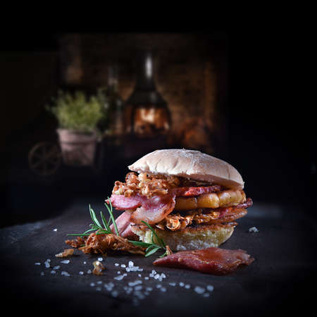 Delicious rustic smoked bacon burger with caramelized onions served with a rosemary herb garnish. Shot against a dark farmhouse background with copy space.