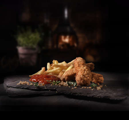 Succulent Chicken Nuggets, or guijons, covered with breadcrumbs, American style French fries and tomato ketchup and thyme herbs shot against a rustic background with generous accommodation for copy space.