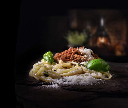 Authentic Italian family recipe bolognese sauce with steamed spaghetti with basil herb and grated Parmesan cheese garnish shot against a dark, rustic background with generous accommodation for copy sp 写真素材