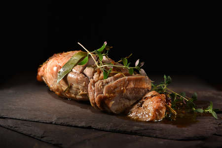 Roasted pork loin fillet with bay leaves, thyme and rosemary herb garnish, carved and ready to serve. The perfect image for your restaurant menu cover art with generous accommodation for copy space. 版權商用圖片