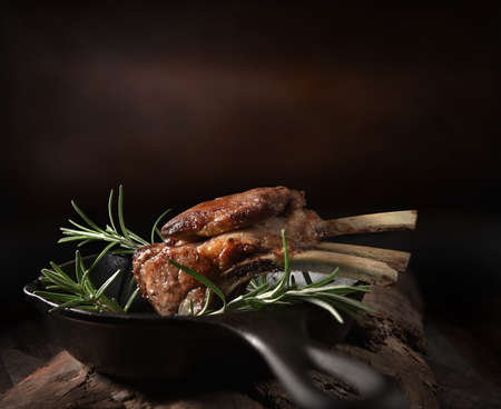 Traditional, roasted rack of lamb cutlets in a wrought iron skillet with rosemary herbs shot against a dark, rustic background with generous accommodation for copy space. Stok Fotoğraf