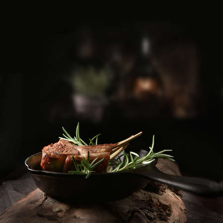 Traditional, roasted rack of lamb cutlets in a wrought iron skillet with rosemary herbs shot against a dark, rustic background with generous accommodation for copy space. Stok Fotoğraf - 140935257
