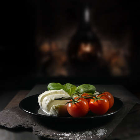 Classic Italian mozzarella cheese served with vine tomatoes and basil herbs shot against a rustic dark background with generous accommodation for copy space. Stock Photo