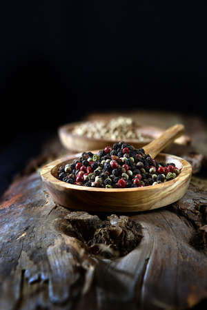 Mixed Mediterranean rainbow peppercorn seeds shot in a rustic setting with dark creative lighting with generous accommodation for copy space. The perfect image for your cooking book cover art. 免版税图像
