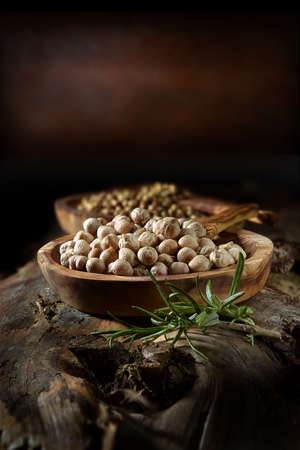 Rustic, creatively lit organic quinoa grains in a wooden bowl with selective focus and generous accommodation for copy space. The perfect image for your vegan recipe bookcover art.