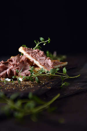Traditional chicken liver pate with fresh thyme herbs shot on old slate  against a black background with generous accommodation for copy space. The perfect image for your bistro or book cover art designs. Imagens
