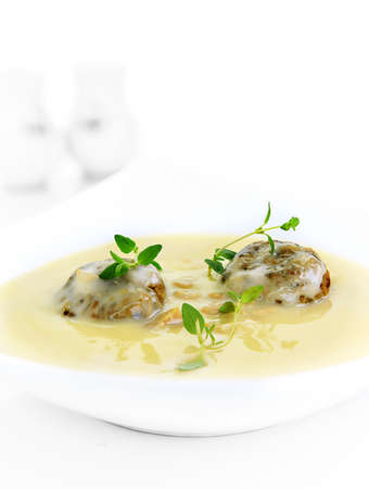 Rich creamy chicken soup with sage and onion stuffing ball dumplings with fresh thyme herb garnish. Shot against a white background with accommodation for copy space.
