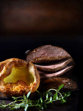 Traditional Sunday roast lunch, prime roast beef with Yorkshire puddings and thyme garnish shot against a rustic background with copy space.