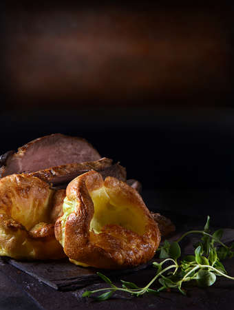 Traditional British Yorkshire puddings served with prime roast beef and thyme herb garnish. Shot against a rustic background with copy space.