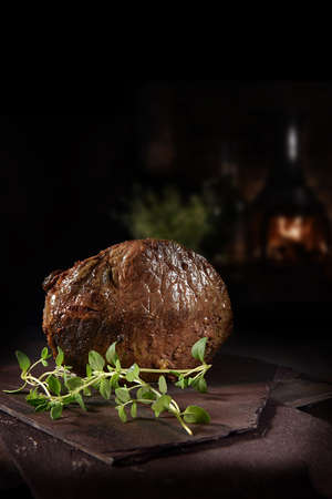 Classic prime roast of beef with thyme garnish shot against a dark, rustic background with generous accommodation for copy space.