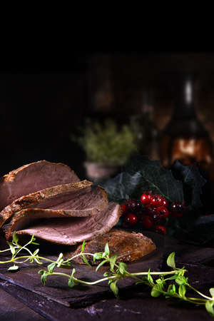 Sliced prime roast beef ready for serving shot against a festive and dark background with copy space.