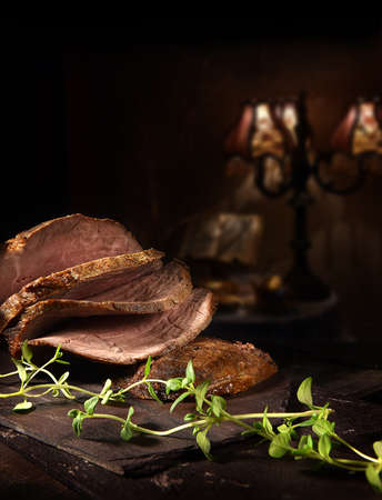 Prime roast beef, sliced and ready to serve with thyme herb garnish. Shot against a rustic background with generous accommodation for copy space.