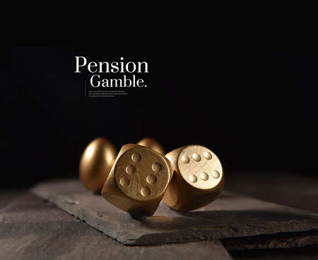 New and unique concept image created to represent pension and investments risks. Creatively lit image of two tumbling dice and gold pension eggs against a black background with copy space.