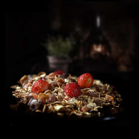 Healthy breakfast concept image, oat, dried fruits, nuts and fresh fruit shot against a dark, rustic background with accommodation for copy space.
