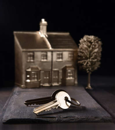 Concept image for new home ownership, purchase. Gold keys and house in background with accommodation for copy space.