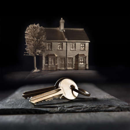 Concept image for new home purchase, gold keys and gold tinted home in the background. Generous accommodation of copy space.
