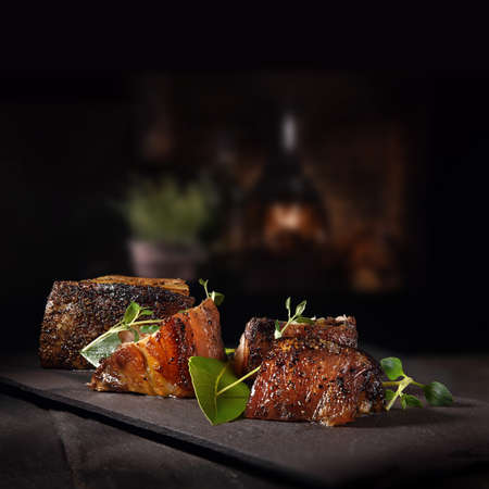 Chinese Szechuan Pork with thyme and bay leaves shot against a dark rustic background with accommodation for copy space.