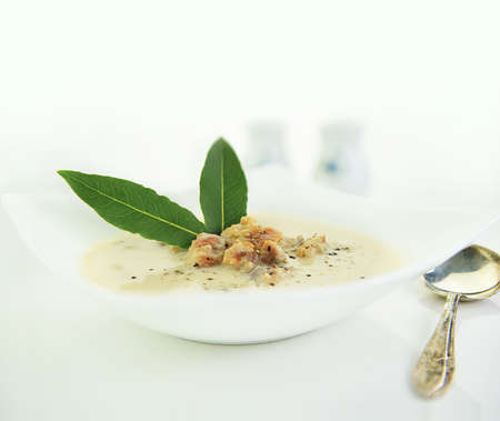 Original and authentic Cullen Skink chowder served with fresh bay leaves and shot against a bright background with generous accommodation for copy space.