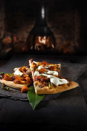 American Texan BBQ chicken pizza served with fresh bay leaves and shot against a dark rustic background with generous accommodation for copy space. Standard-Bild