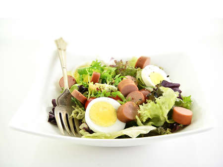 Healthy fresh green salad with sliced boiled eggs and chopped frankfurter sausages with seasoning and cashew nut garnish. Shot against a bright, white background with copy space. Standard-Bild
