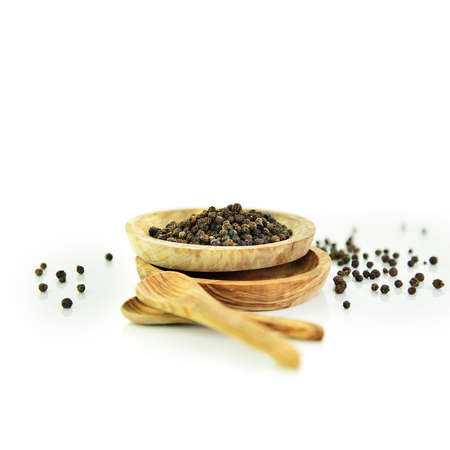 Close-up of organic whole black peppercorns in a small wooden staked  dish with differential focus. Shot against a white background with copy space. Concept image for cooking and food preparation. Standard-Bild