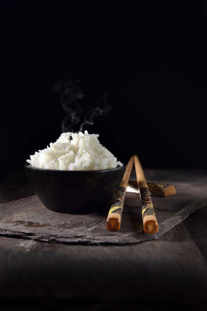 Basmati rice steaming in a small black ceramic crucible with genuine antique hand-decorated bamboo chop sticks on black slate. Shot against a black background with generous accommodation for copy space.
