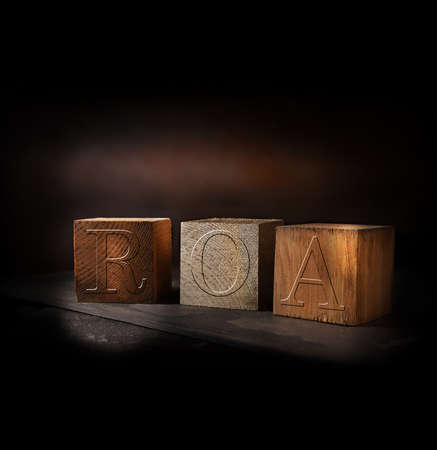 Concept-image for Return On Assets termed ROA or RONA. Stained and gold wooden blocks with embossed initials of ROA shot against a rustic background with accommodation for copy space. Standard-Bild