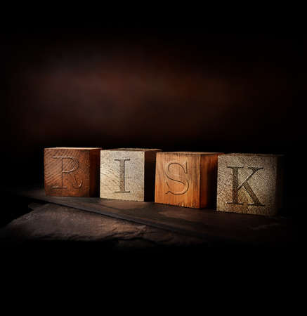 Concept image for RISK. Dark oak stained and gold wooden blocks with embossed initials of RISK shot against a rustic background with generous accommodation for copy space. Standard-Bild