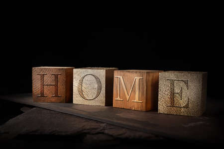 Concept image for HOME. Working from home. Dark oak stained and gold wooden blocks with embossed initials of HOME shot against a rustic background with generous accommodation for copy space. Standard-Bild