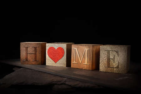 Concept image for loving HOME and working from home. Dark oak stained and gold wooden blocks with embossed initials shot against a rustic background with accommodation for copy space.