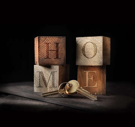 Original concept image for home buying. Rustic, creatively lit wooden blocks and golden keys to signify a home purchase with generous accommodation for copy space.